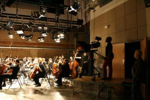 An MCPP student operates a camera during the orchestral performance of Bohemian Rhapsody