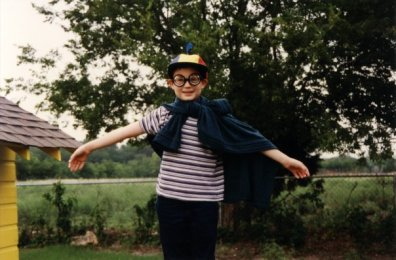 """Anthony Almond: """"I guess you could say I was a little brainiac. In that picture, it's obvious from my glasses, lab coat, and hat that I'm dressed as a scientist. I would always do mini science experiments as a kid too. I had a book called simple science experiment with everyday materials. Sadly I was never able to prove the existence of the Higgs Boson with my experiments. I would also build things with Legos, Lincoln Logs, and Erector Sets then run simulations with the models I made. I was always striving for the best fit Lego model of real life. Clearly I chose the right career path. My child self would be very proud. """""""