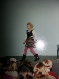 """Glenna Read: """"This picture is from a piano recital. I think I was about 8. The outfit is characteristic of my style at that time. I would only wear boots and was really into vests. I also had to cut some gum out of my hair around that time and that's how I ended up with such a short hairstyle."""""""