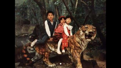 """Jingjing Han: """"This photo was when we were in a local zoo. The tiger now is more than thirty years old! I was a scientific nerd. I was always looking for the reality in my toys."""""""