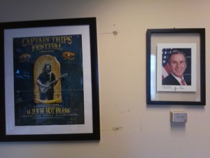 Julien's Wall of Cognitive Dissonance, which includes a Dead poster and a signed Bush photo
