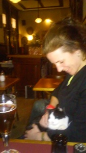 "Irene in a ""brown cafe"" with a local bar cat"