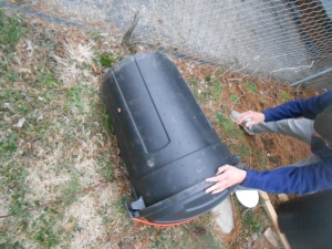 "Ben ""turning' the compost bin which basically means rolling it around on the ground."